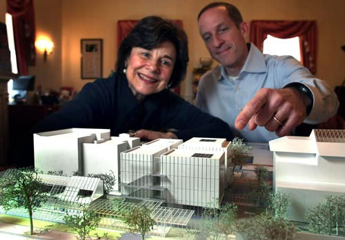 Gardner Museums director Anne Hawley and Jim Labeck, the director of operations, look over a 3-D model of the Gardner museum's new wing (center). That's an existing apartment building at left. The original building (right) sits in front of it facing the Fenway.