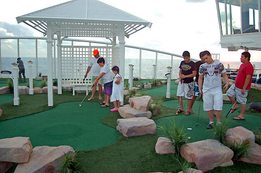 Cruise-goers play mini-golf on the sports deck of the Oasis.