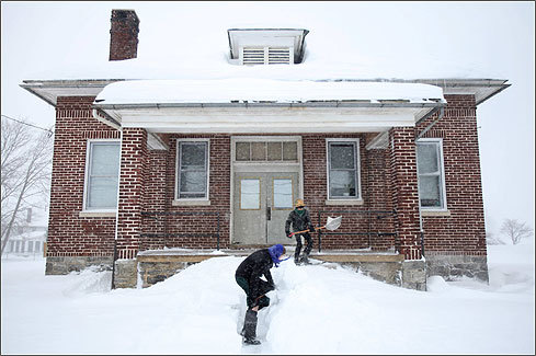 An Amish boy (rear) and a woman shoveled snow at the Fairview Amish School in Ronks, Pa.