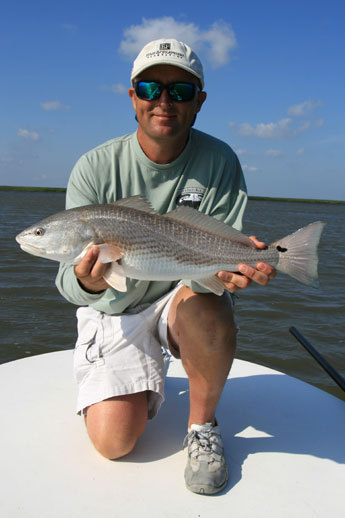 Dykes poses with a red before quickly releasing it. In the background, Sapelo Sound stretches emptily like a private fishing universe, which it is many days of the year.