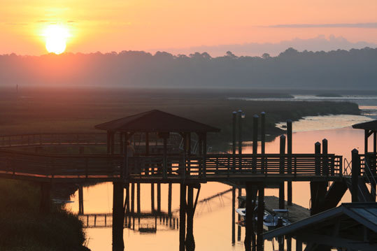 "From the water, the Bluffs rise out of the spartina grass on the Julienton and Broro rivers, frequented by Georgian anglers for over a century. Shown, a lemon sun rises on ""downtown"" Shellman's waterfront of boat lifts and the Shellman Fish Camp store where a Coke costs 60 cents."