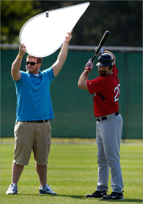 Red Sox videographer Tim Heintzelman held a reflector for a photo shoot of Red Sox first baseman Kevin Youkilis.