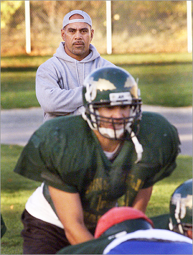 Tatupu's son, Lofa, played quarterback during his father's time as coach at King Philip. Pictured: Lofa took a snap as his father looked on in November 2000.