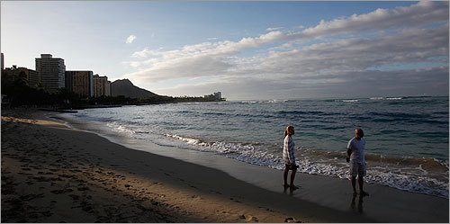 The serene scene at Waikiki Beach belied the impending tsunami threat. Teresa Burge and Bill Bodnar of Calgary, Alberta, Canada enjoyed a morning stroll.