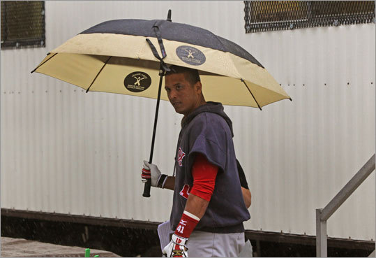 Catcher Victor Martinez used an umbrella to stay dry Tuesday, when rain pushed the Sox' workouts indoors.