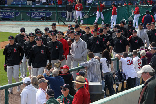 Northeastern players watched the Red Sox take BP, then headed to the outfield to regroup.