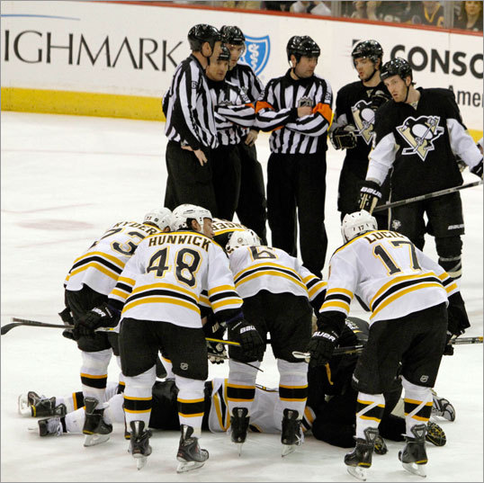 Bruins players surrounded Marc Savard as he was unable to move on the ice.