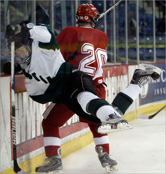 Austin Prep's Shane Hurley was checked into the boards by Hingham's Austin O'Connor (20) during their Super 8 pool game.