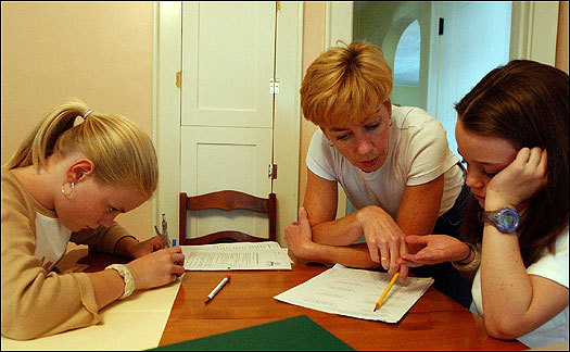Tricia Verrier overseeing homework with her daughters, Emily (left) and Sarah, in their kitchen.