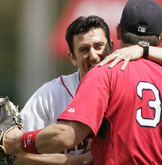 Garciaparra (left) who signed a one-day minor league contract, hugs Red Sox catcher Jason Varitek fter throwing out a ceremonial first pitch at City of Palms Park on Wednesday.