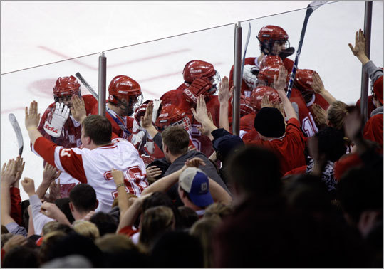 Hingham players celebrated with their fans at the glass after winning the game against Malden Catholic.