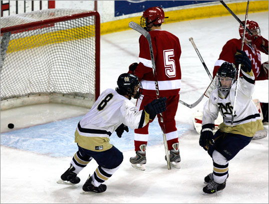 Malden Catholic players Mike Vecchione (8) and Brendan Collier celebrated after teammate Justin Sencabaugh (not pictured) scored a goal late in the third period to send the game into overtime as Hingham's Andrew Sypek (5) looks on.