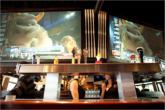 A view of two 6½-by-11-foot high-definition TV sets above the center of a 44-seat mahogany bar at Remy's.