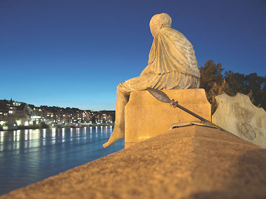 A statue of Helvetia gazes past Basel's French and German borders.