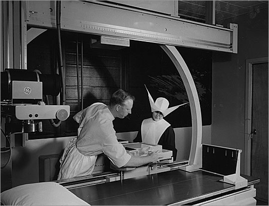 An X-ray technician explains how a new X-ray machine works to a nun in Carney Hospital in 1954.