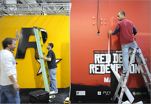 Cem Inci, right, Dennis Whitaker, left, and Michael Keogh set up the Rockstar Games booth Thursday night.