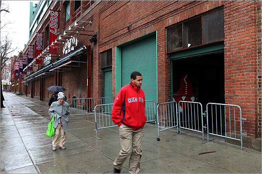 A man wore a Red Sox coat as he walked down the rain-soaked sidewalk passing Fenway Park.