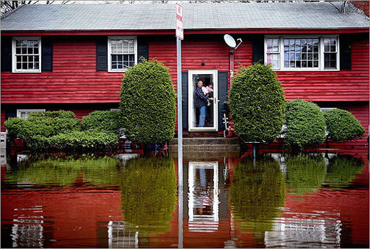 Dana Knight and his daughter, Emily, 2, surveyed the waters surrounding their home in Framingham.