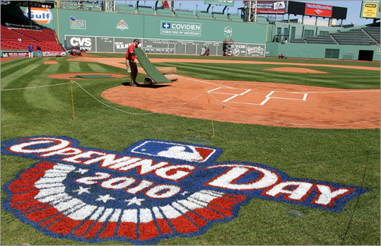 Preparations for opening Day are underway at Fenway Park. A grounds keeper works near home plate.