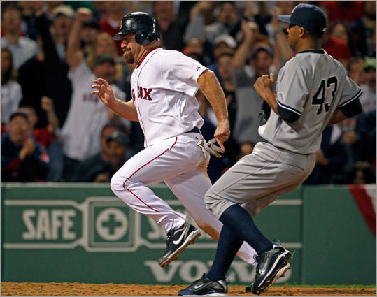 Kevin Youkilis put the Red Sox ahead 8-7 in the seventh inning when he scored from third on a passed ball. Yankees pitcher Damaso Marte is at right.