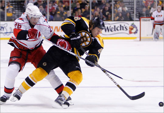 Carolina Hurricanes' Erik Cole, left, and Boston Bruins' Matt Hunwick battle for the puck during the first period Saturday at the Garden.