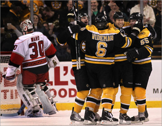 Bruins left wing Steve Begin (27) was surrounded by his celebratory teammates after scoring the Bruins' third short-handed goal in the second period, which proved to be the eventual game winner.