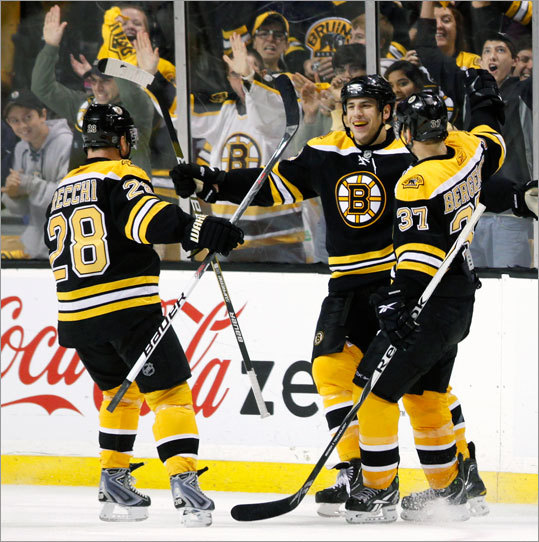 The Bruins' Milan Lucic, center, celebrated his empty-net goal with teammates Mark Recchi (28) and Patrice Bergeron (37) during the third period Saturday. The Bruins won 4-2 and clinched a playoff berth.