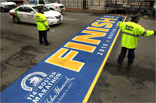 The finish line to the Boston Marathon was put down on Boyston Street in front of the Boston Public Library on Thursday. On Friday, Boston Police directed traffic as staging was erected around it. The line is normally placed on the Saturday before the race, but this year the plan was changed because of the weather.