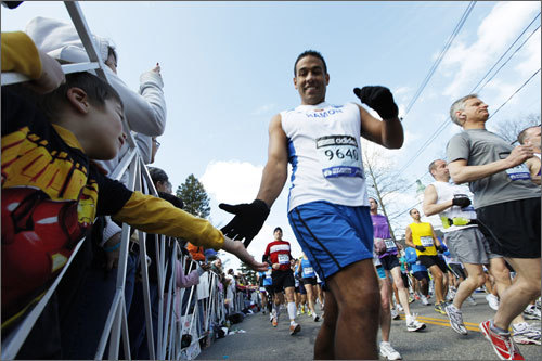 Liam Higgins, 5, of Hopkinton reaches out for high-fives as the first wave of runners take off from the starting line.