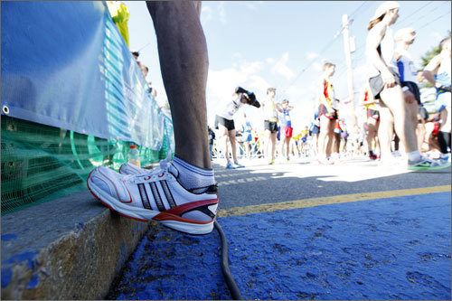 Racer No. 105 of the men's elite runners stretched his calves before the start of the race.