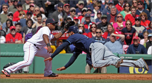 Red Sox third baseman Adrian Beltre awaited the throw as the Tampa Bay Rays Carlos Pena dove ahead of the throw during the second inning in the Patriots Day game at Fenway.