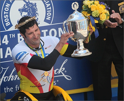 Ernst Van Dyk holds up the spoils after winning his ninth Boston Marathon wheelchair race.