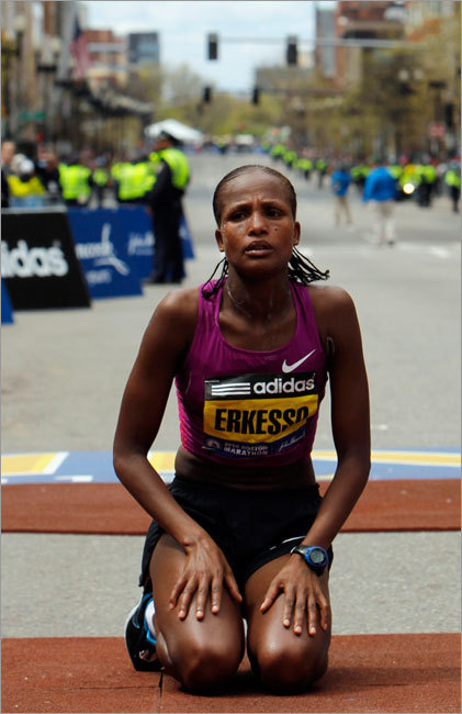 Ethiopia's Teyba Erkesso kneels on the ground after winning the women's division.