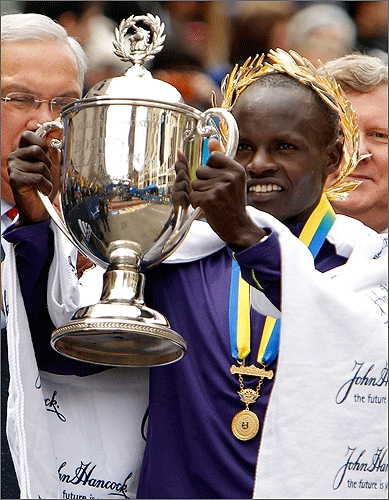 Kenya's Robert Kiprono Cheruiyot, 21, held up the trophy after winning the men's division and setting a new course record.