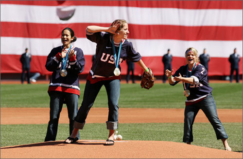 With her silver medal around her neck U.S. Olympic hockey player Meghan Duggan of Peabody listened to the Fenway crowd from the mound as her Team U.S.A. teammates gave her support to throw out the first pitch on Patriots Day.