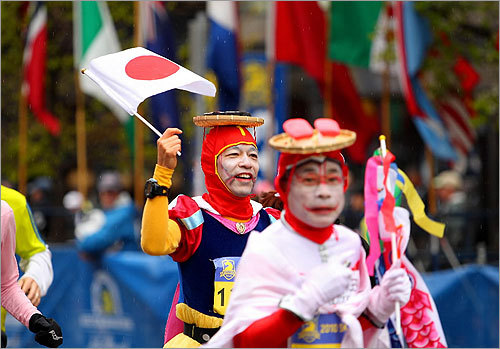 Tetsutomo IIzuka of Japan, waved Japan's flag as he crossed the finish line.