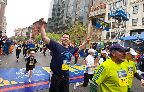 Eric Mitchell of Chicago waved to his wife who cheered him on as he finished the 5K.