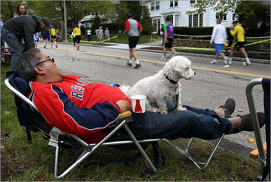 Lenny Crisostomo napped while his dog, Pogi, watched runners climb Heartbreak Hill.