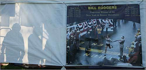 A sign depicting Bill Rodgers's marathon career decorated the side of a tent in Hopkinton Common.