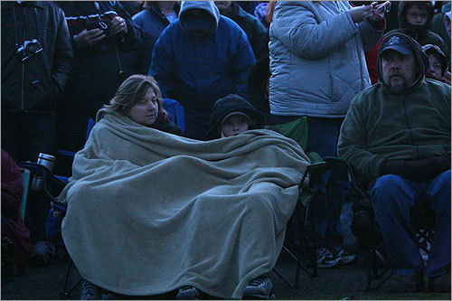 Tracy Flory and son James, 11, of Westford curled up in blankets while awaiting the reenactment.