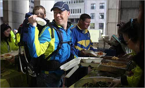 Runner Sage Cowsert gestured to his son, Riley Cowsert, in the pasta line at the Boston Marathon pre-race dinner at City Hall Plaza Sunday. The Cowserts are from Olympia, Wash.