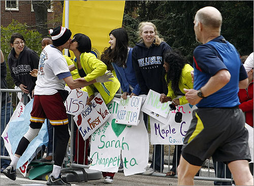 A Wellesley College student gets a smooch from a runner.