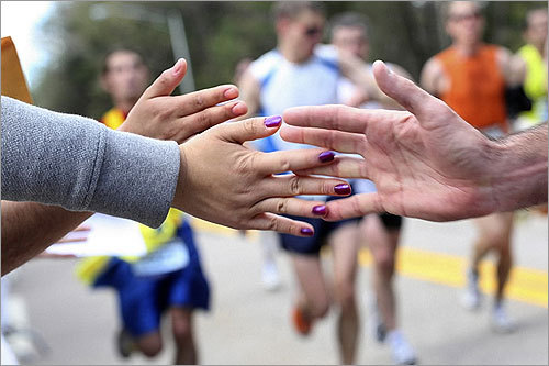 A runner high-fives someone from the crowd.