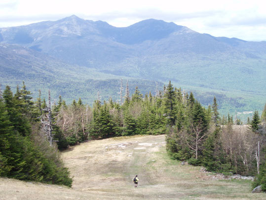 A hiker descends Wildcat Mountain along a ski trail.