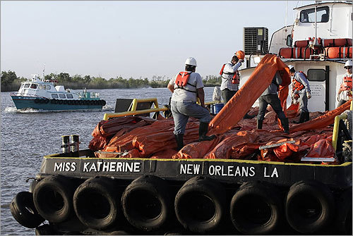 Workers loaded oil booms onto a crew boat.