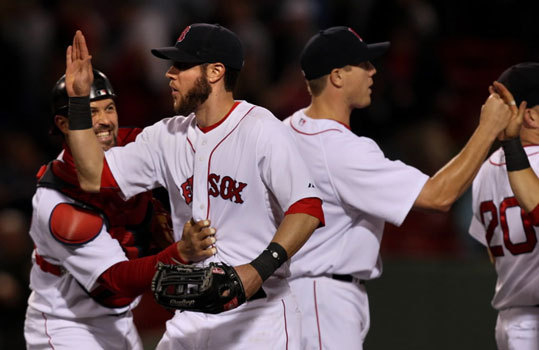 Jeremy Hermida is congratulated by Jason Varitek after Tuesday night's game as Jonathan Papelbon high fives teammates. Hermida doubled in three go ahead runs in the eighth inning and the Red Sox beat the Angels, 5-1.