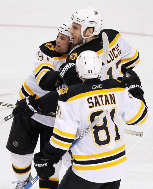 The Bruins' Milan Lucic (center) scored to tie the score at 3-3 in the third period. Marc Savard (left) and Miroslav Satan congratulated him.