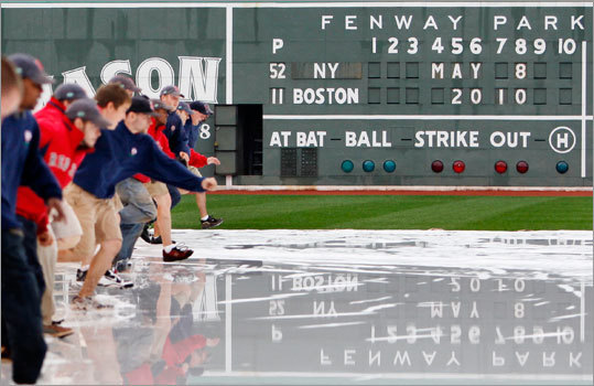 The Fenway Park grounds crew removed the tarp on the field before a baseball game between the Red Sox took on the Yankees.