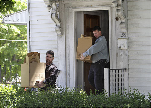 Investigators carried boxes containing bags labeled 'evidence' as they departed the Watertown home.