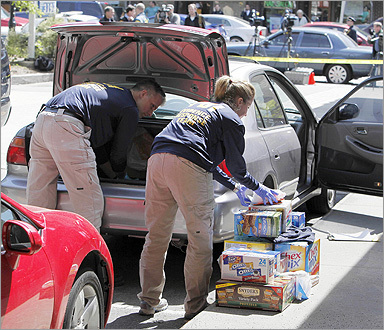 Investigators replaced items they had removed from a car on Harvard Street in Brookline.